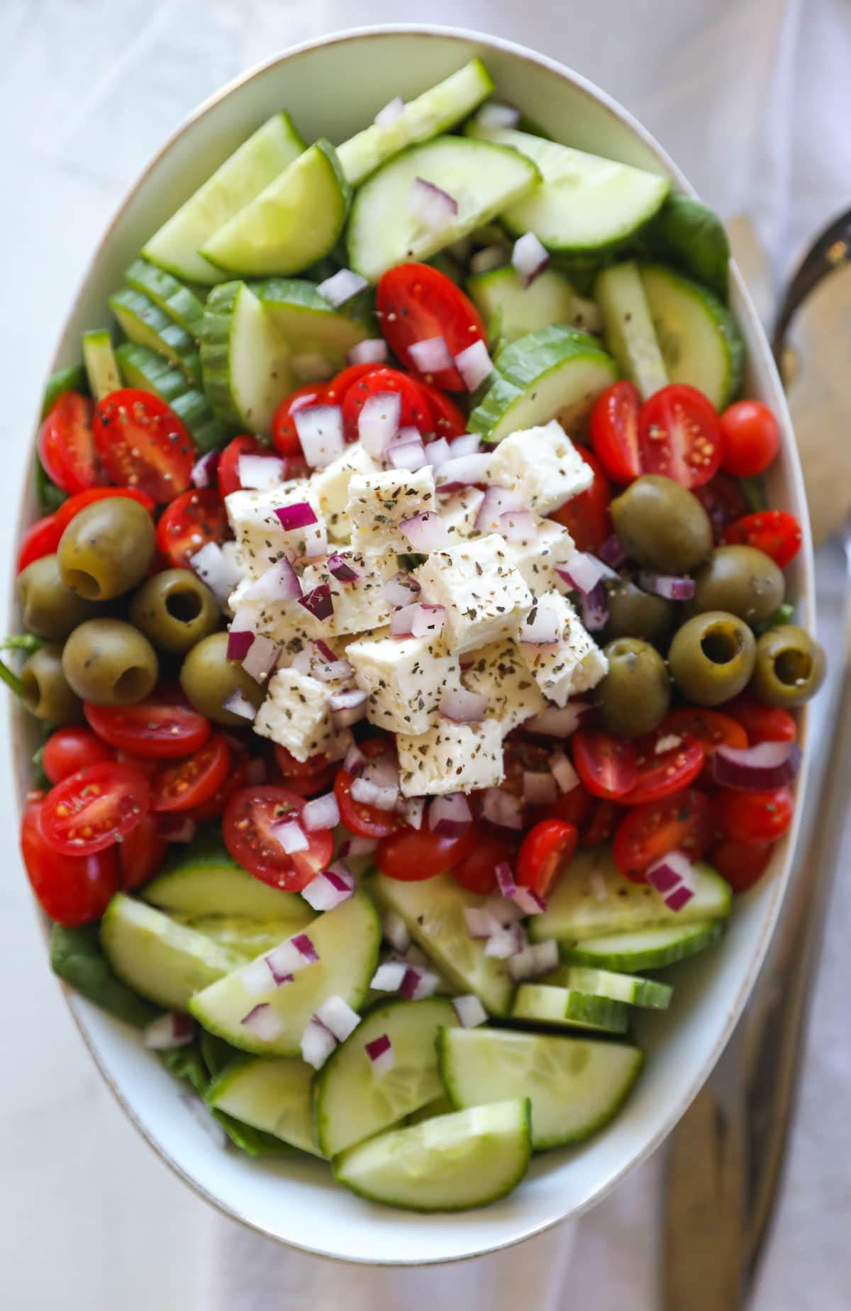 overhead shot of greek salad in oval bowl