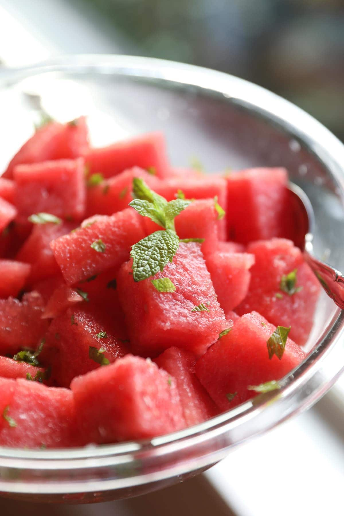 cubes of watermelon in bowl with fresh mint