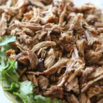 shredded carnitas on platter with cilantro