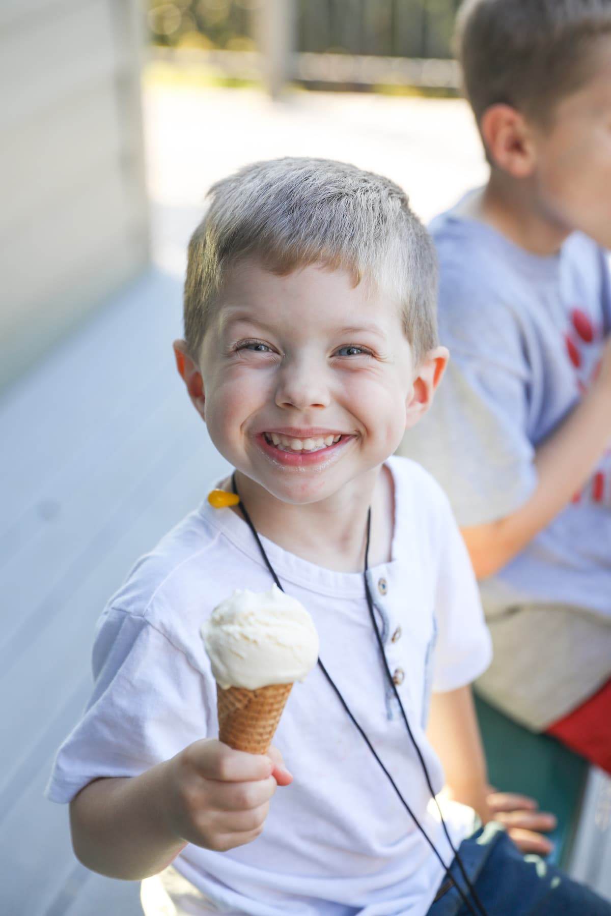 boy smiling holding vanilla ice cream cone