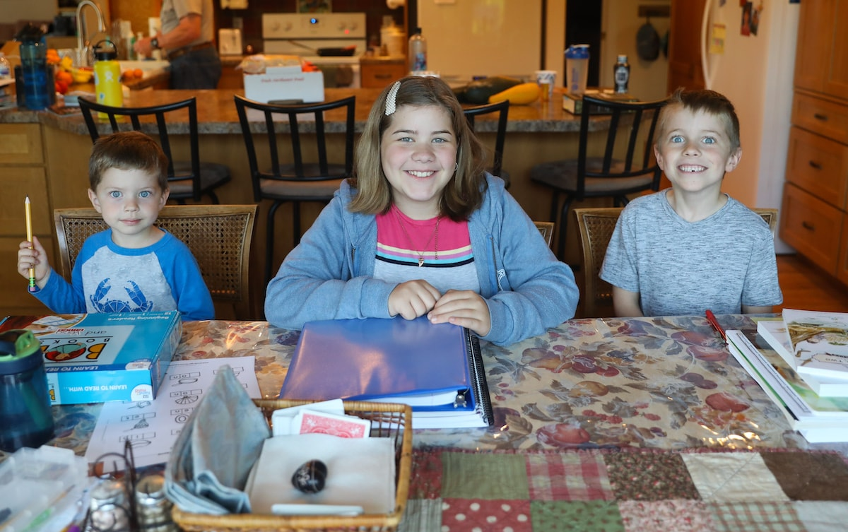 three kids sitting at a table