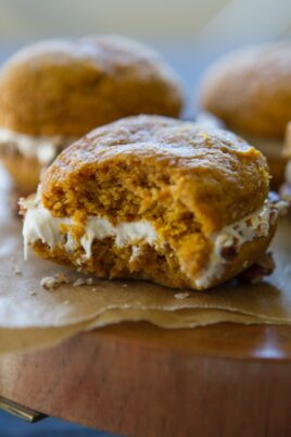 A pumpkin whoopie pie with a bite taken out