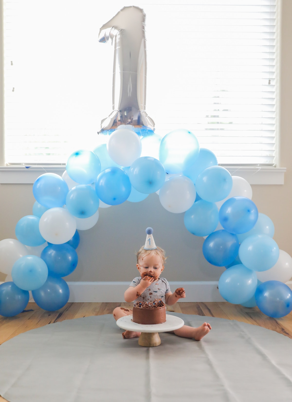 baby sitting under ballon arch with cake