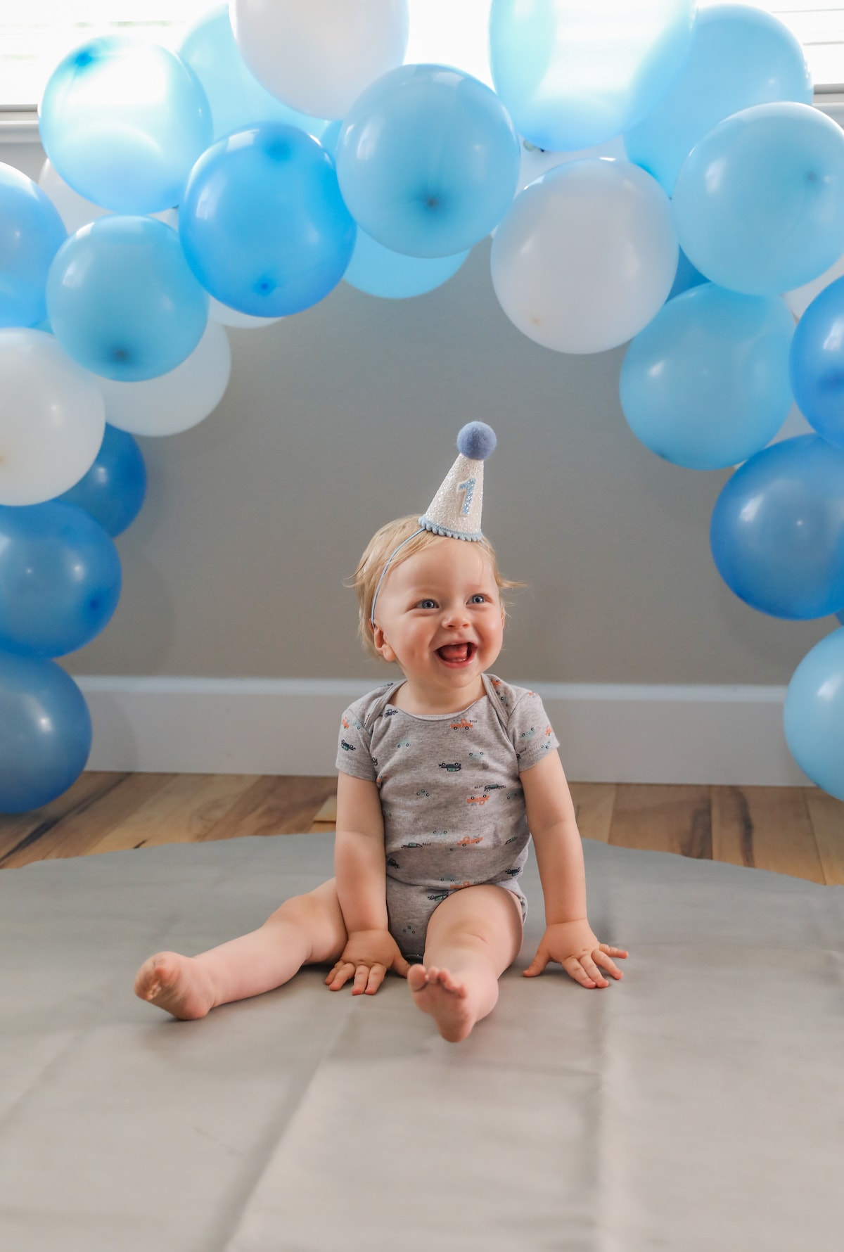 baby smiling under blue balloon arch