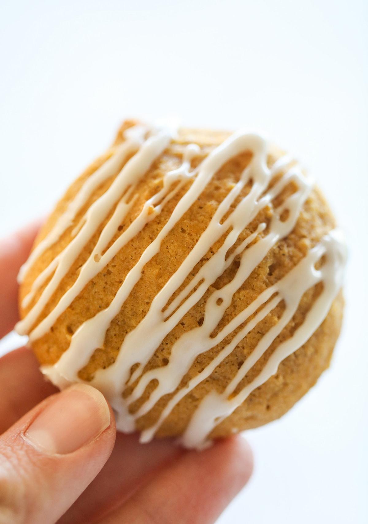 hand holding pumpkin cookie