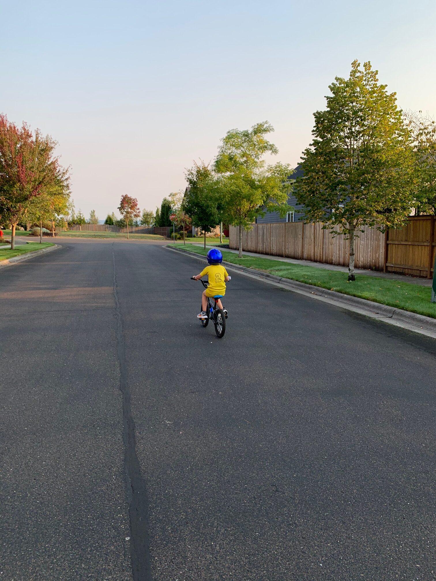 boy riding bike on road