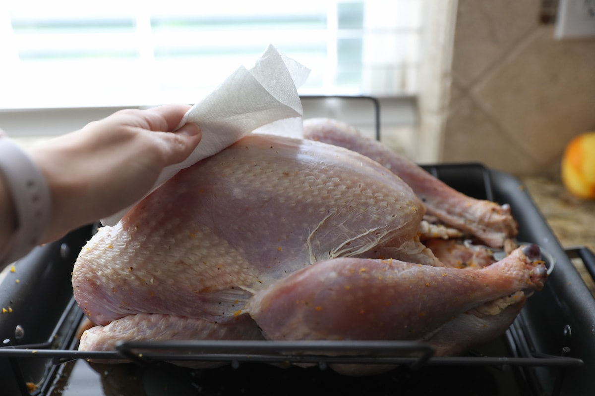 wiping turkey with paper towel