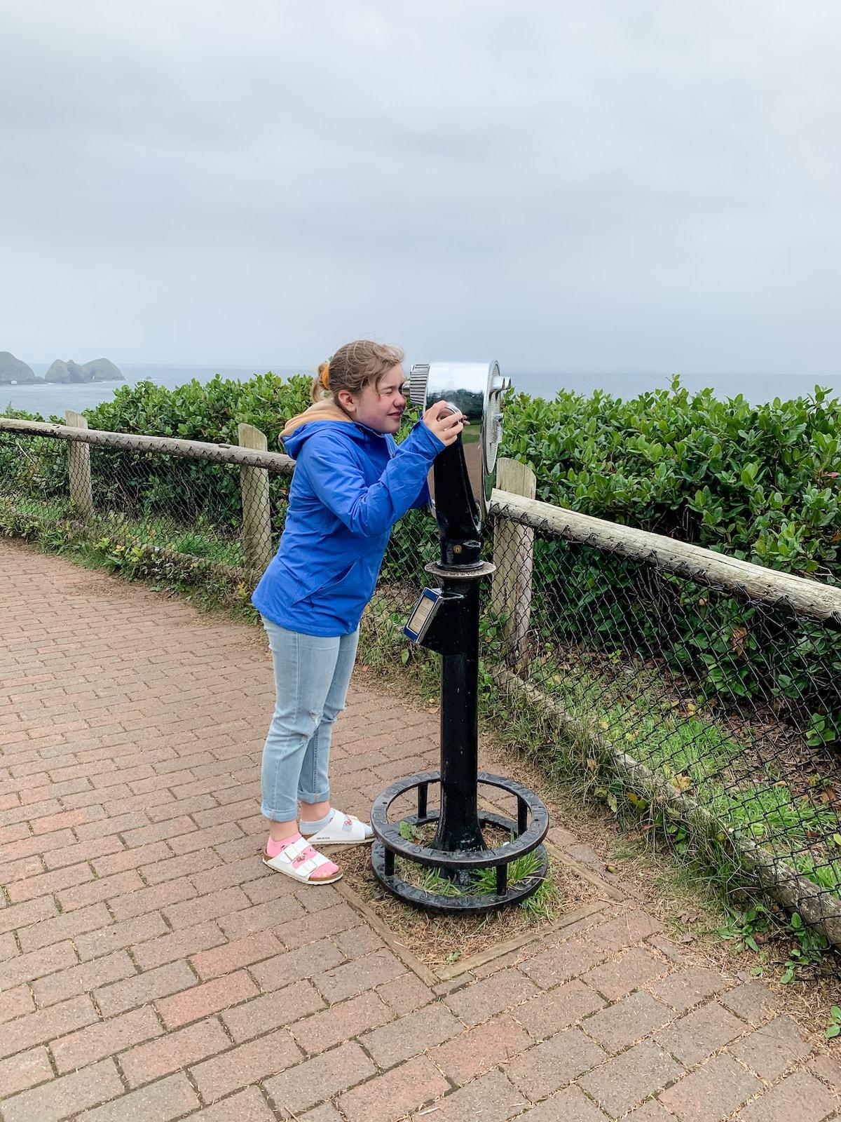 girl looking through coin operated binoculars