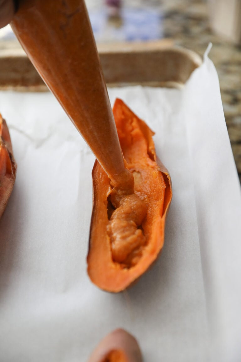 piping sweet potato mixture into potato skins