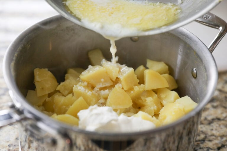 pouring butter, milk and garlic into poatoes
