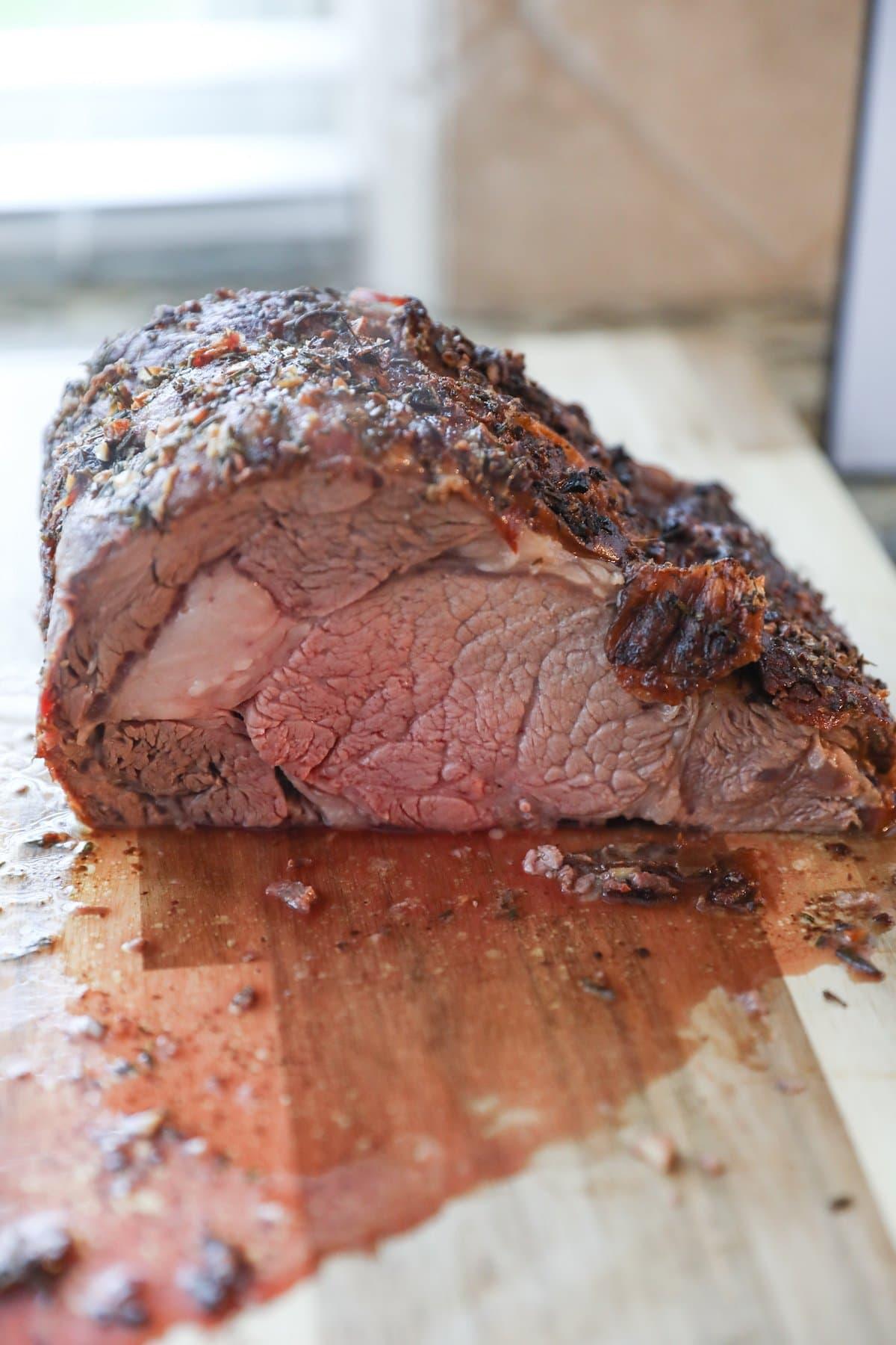 cut prime rib on wooden cutting board