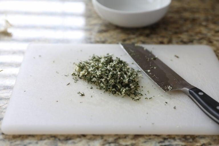 chopped garlic and herbs on cutting board