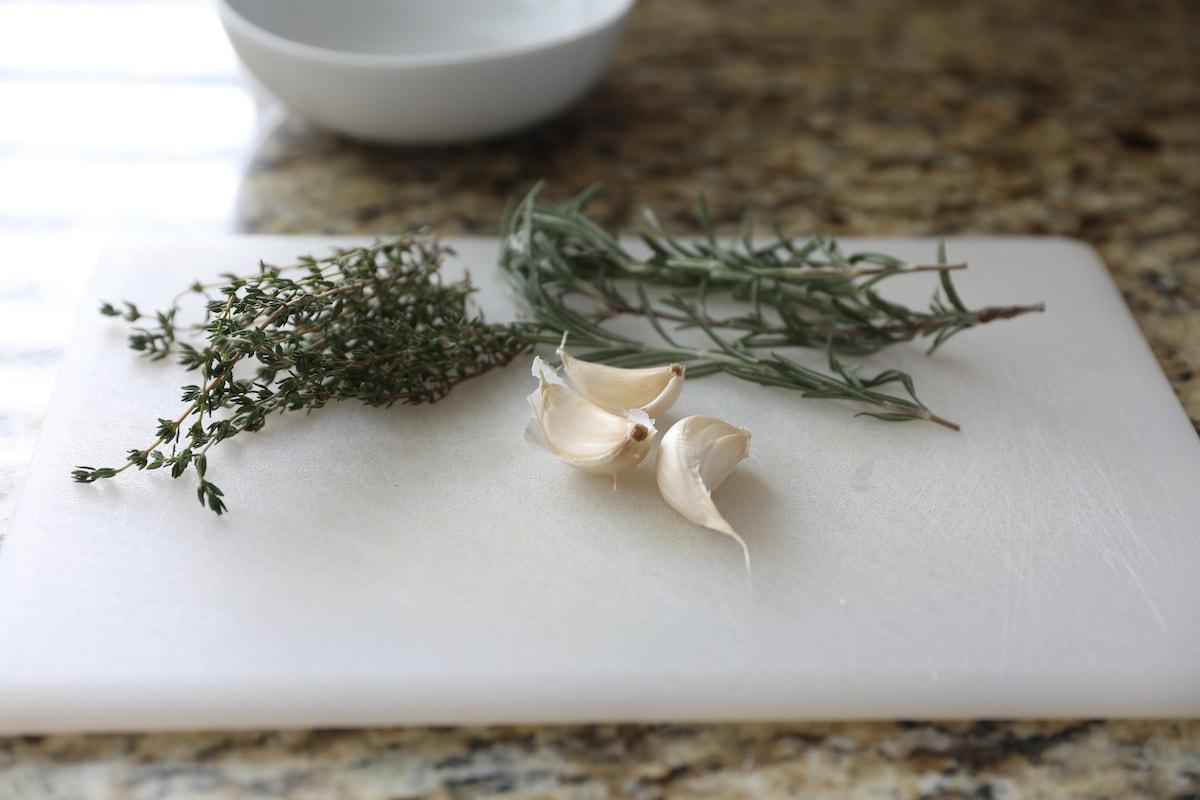 garlic cloves, fresh rosemary and fresh thyme on cutting board
