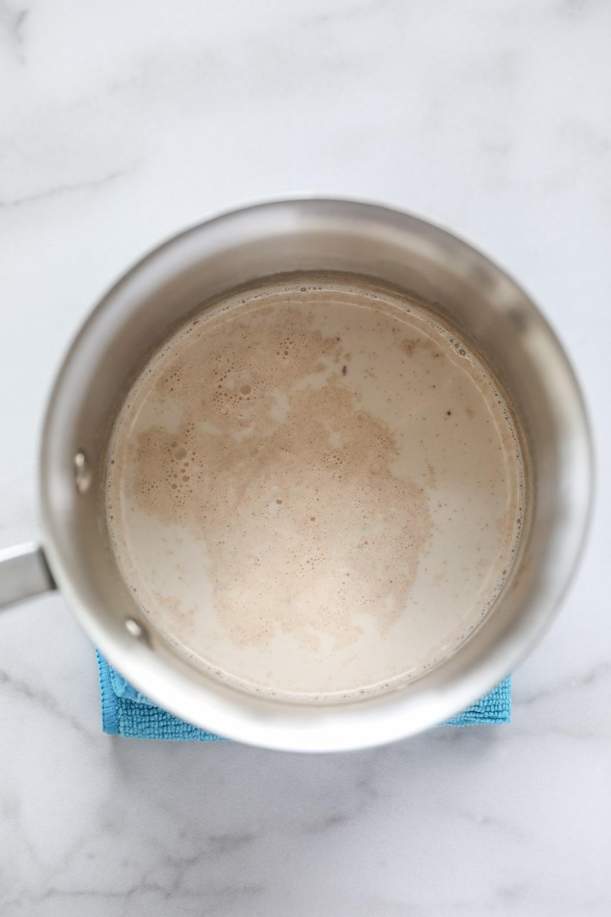 hot milk, cinnamon and nutmeg in saucepan