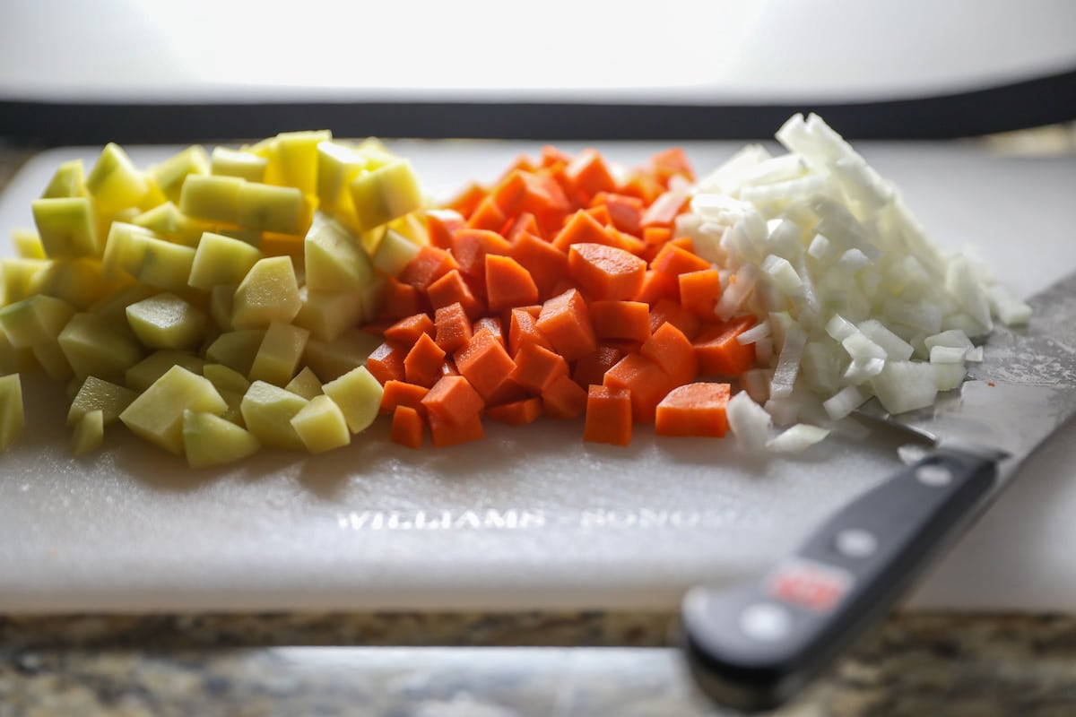 chopped potato, carrots and onions on cutting board