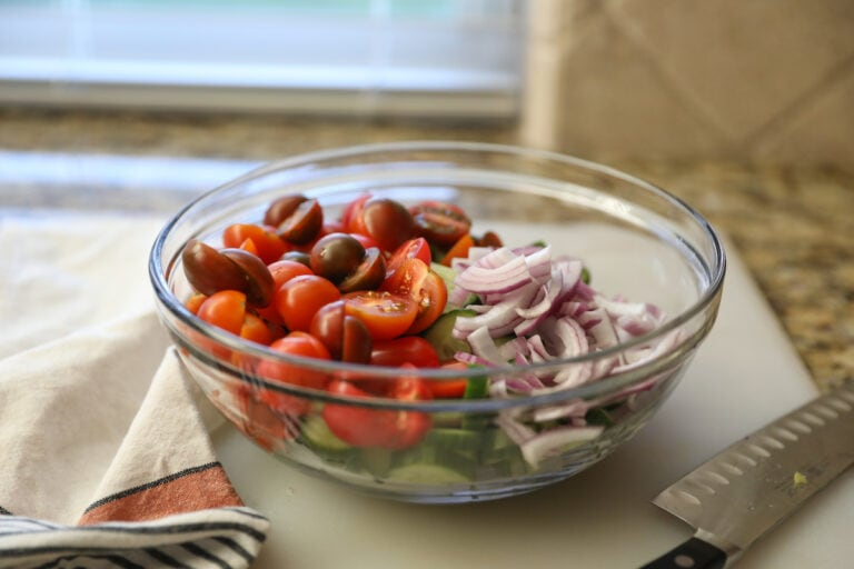tomatoes, onions and cucumber in glass bowl