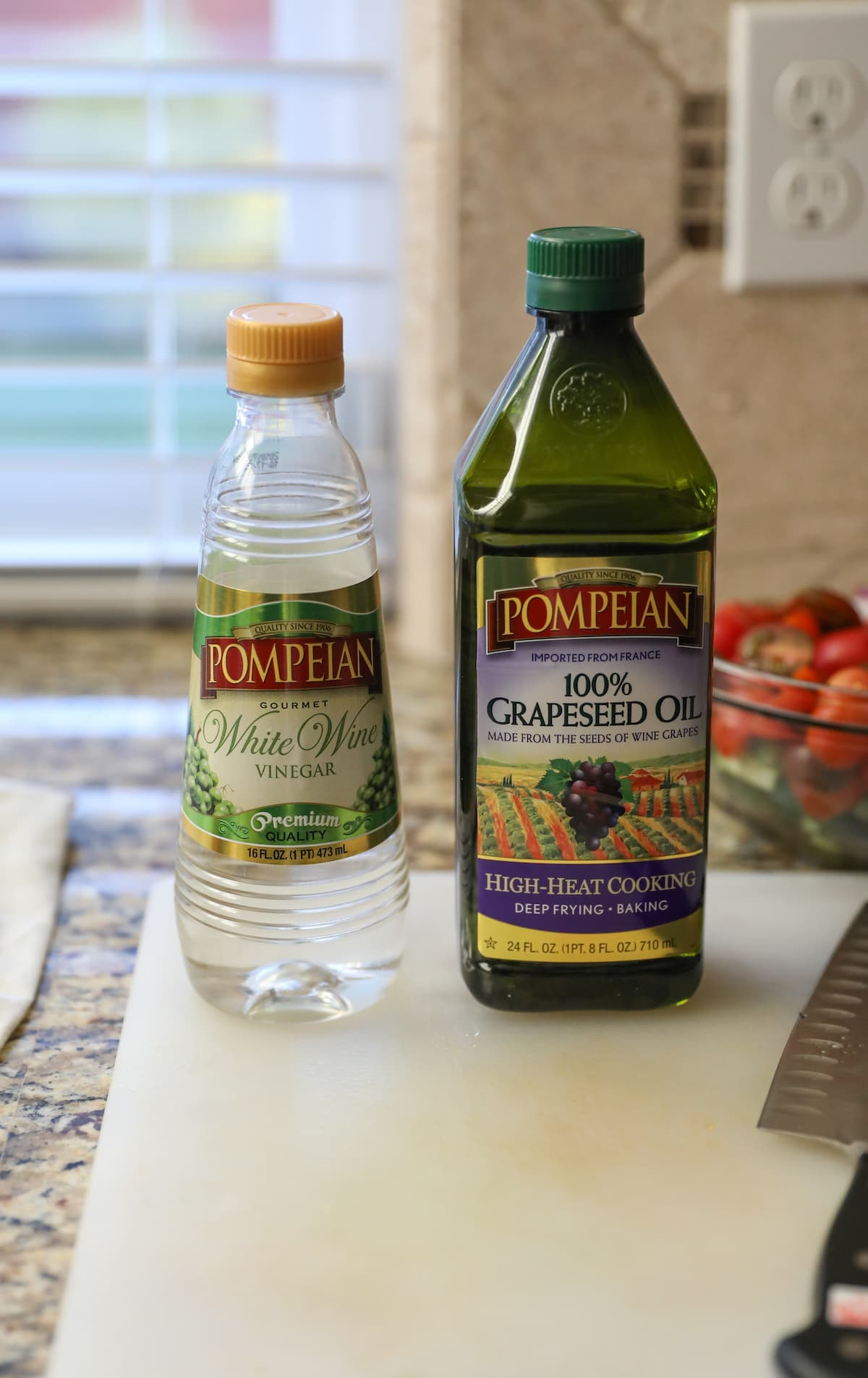 bottles of vinegar and oil on cutting board