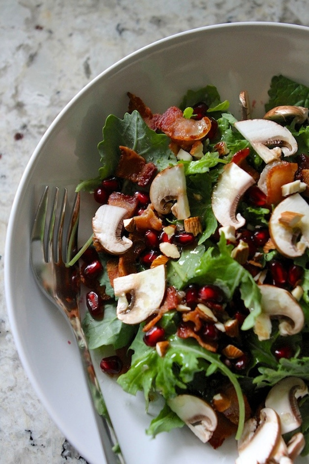 pomegranate salad in a white bowl with fork