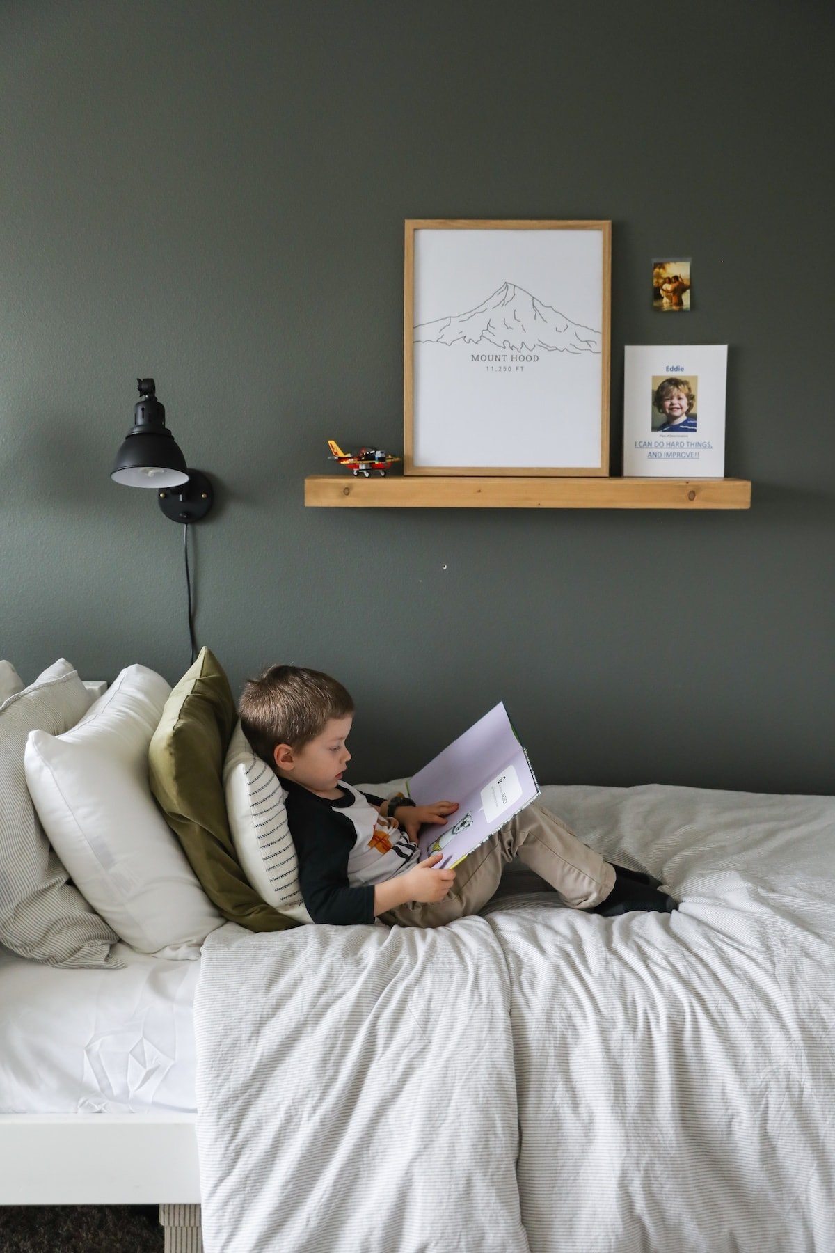 boy reading book on bed