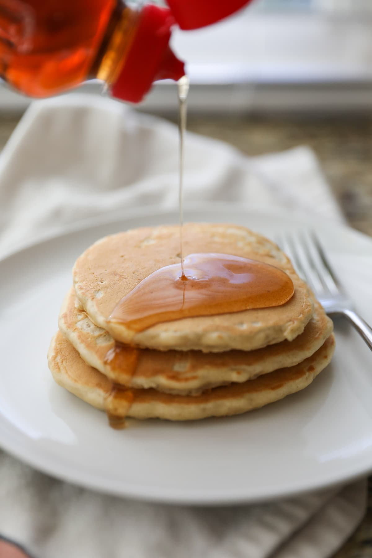 pouring syrup on oatmeal pancakes