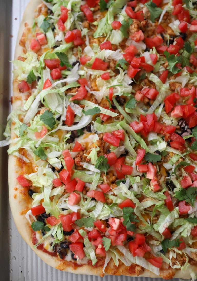 taco pizza topped with lettuce and tomato