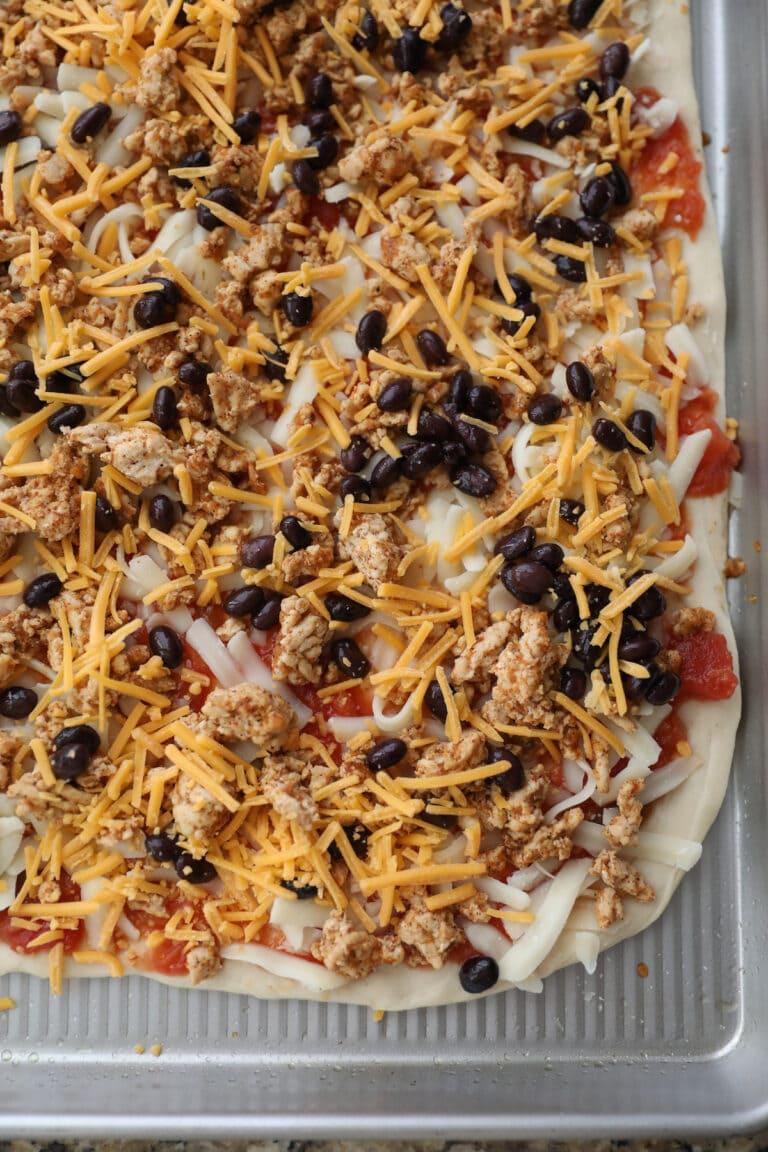 unbaked taco pizza on baking sheet