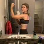 lady flexing in bathroom mirror