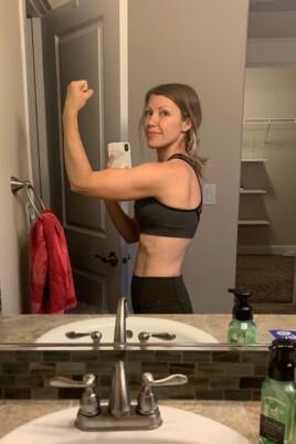 lady flexing in bathroom mirror