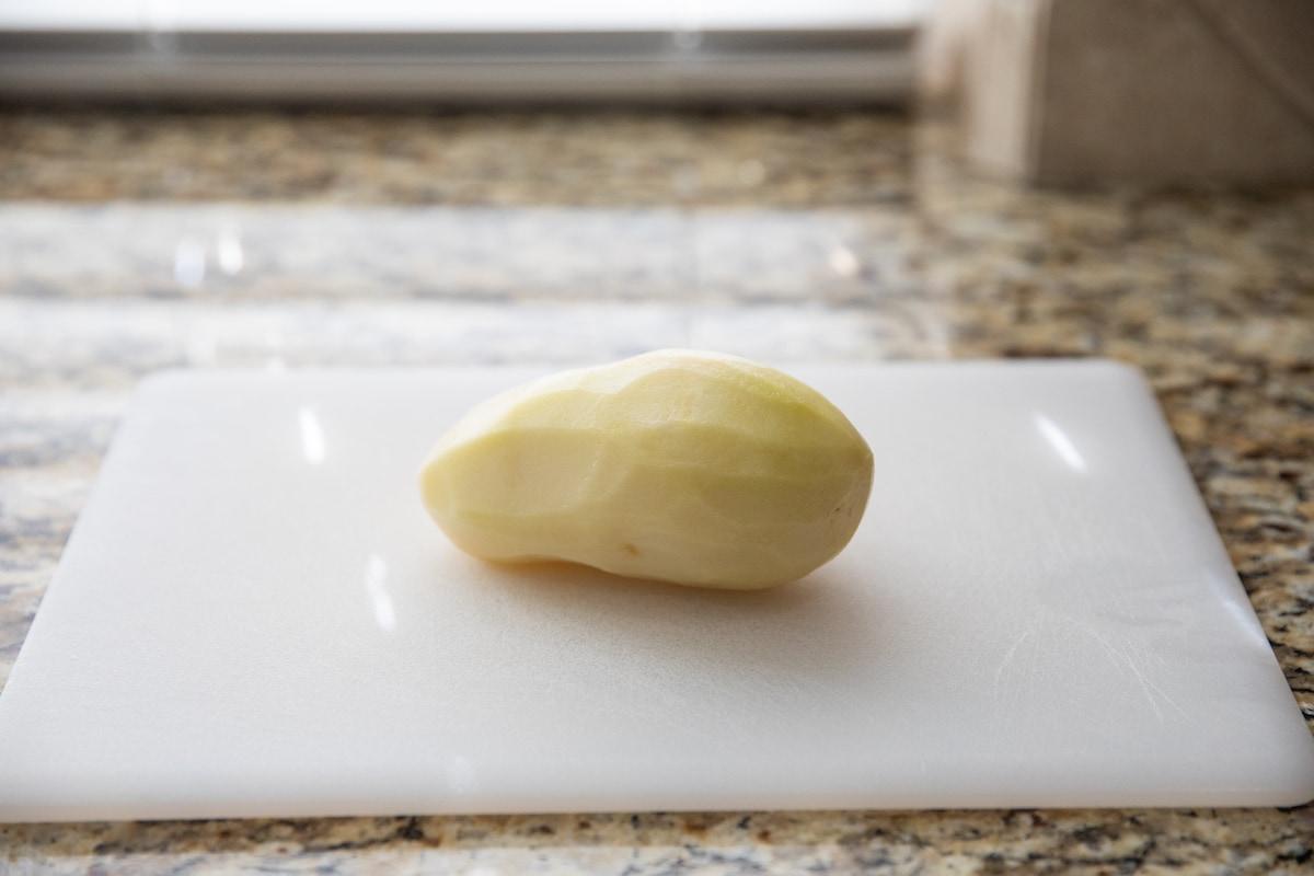 peeled potato on cutting board