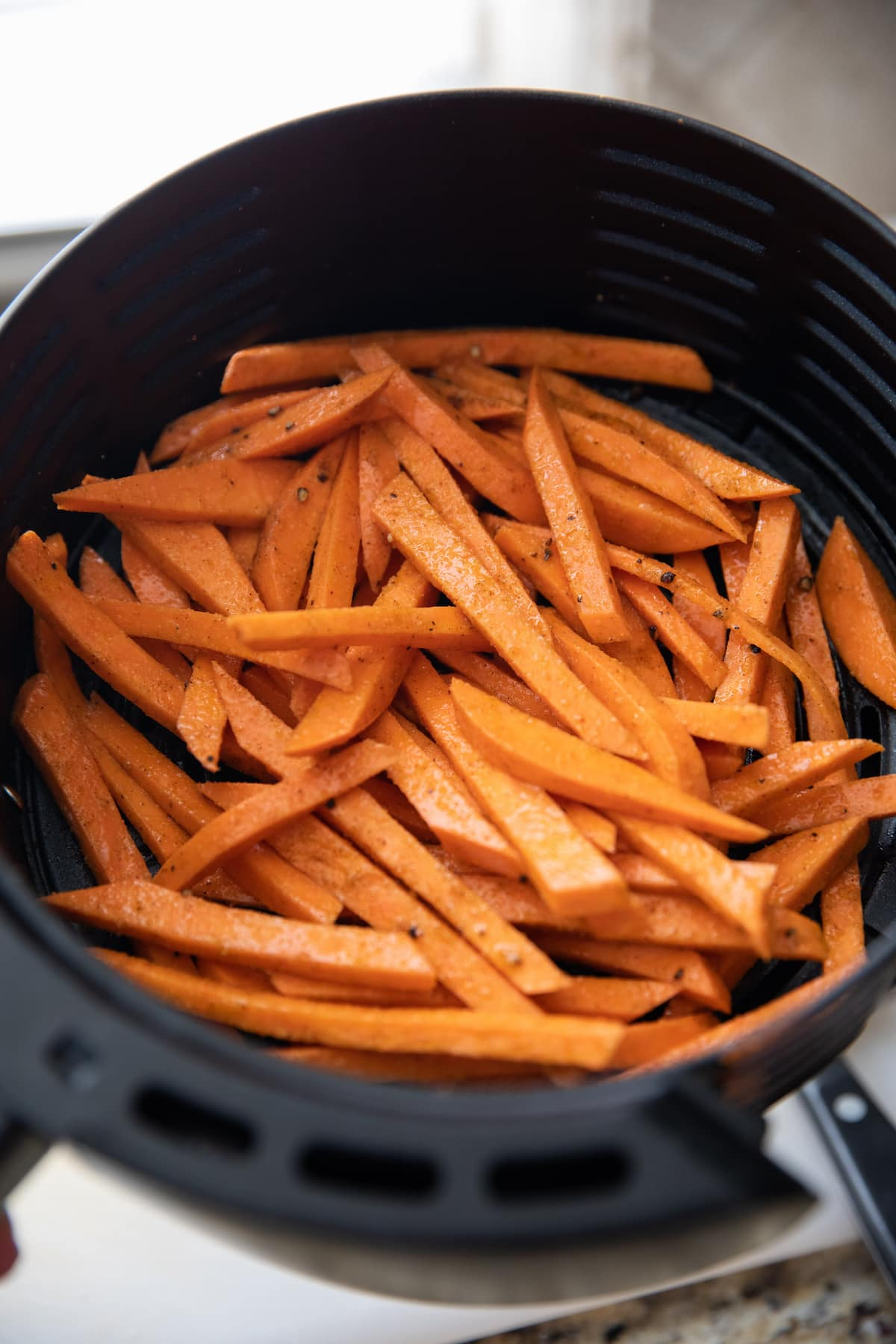 unbaked sweet potato fries in air fryer basket