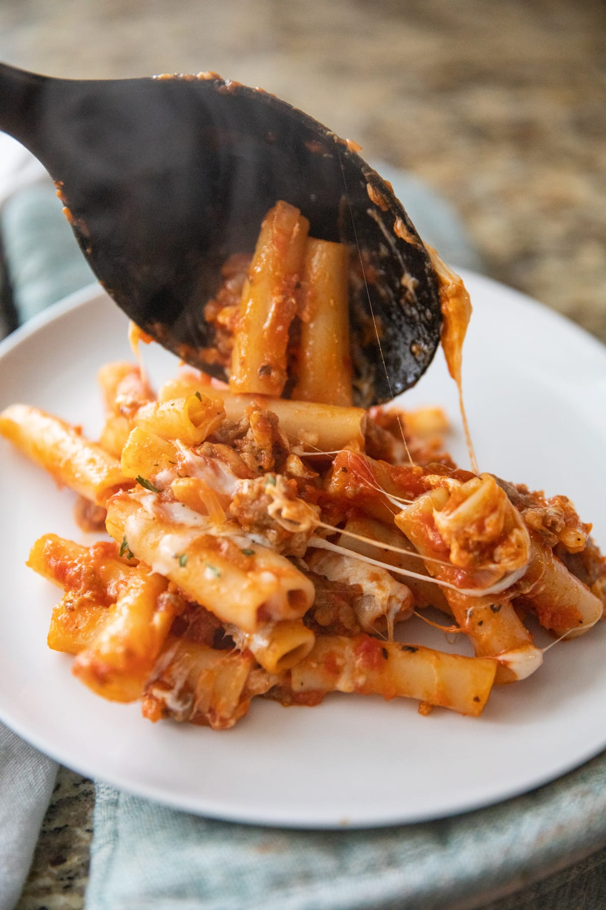 spooning baked ziti onto white plate