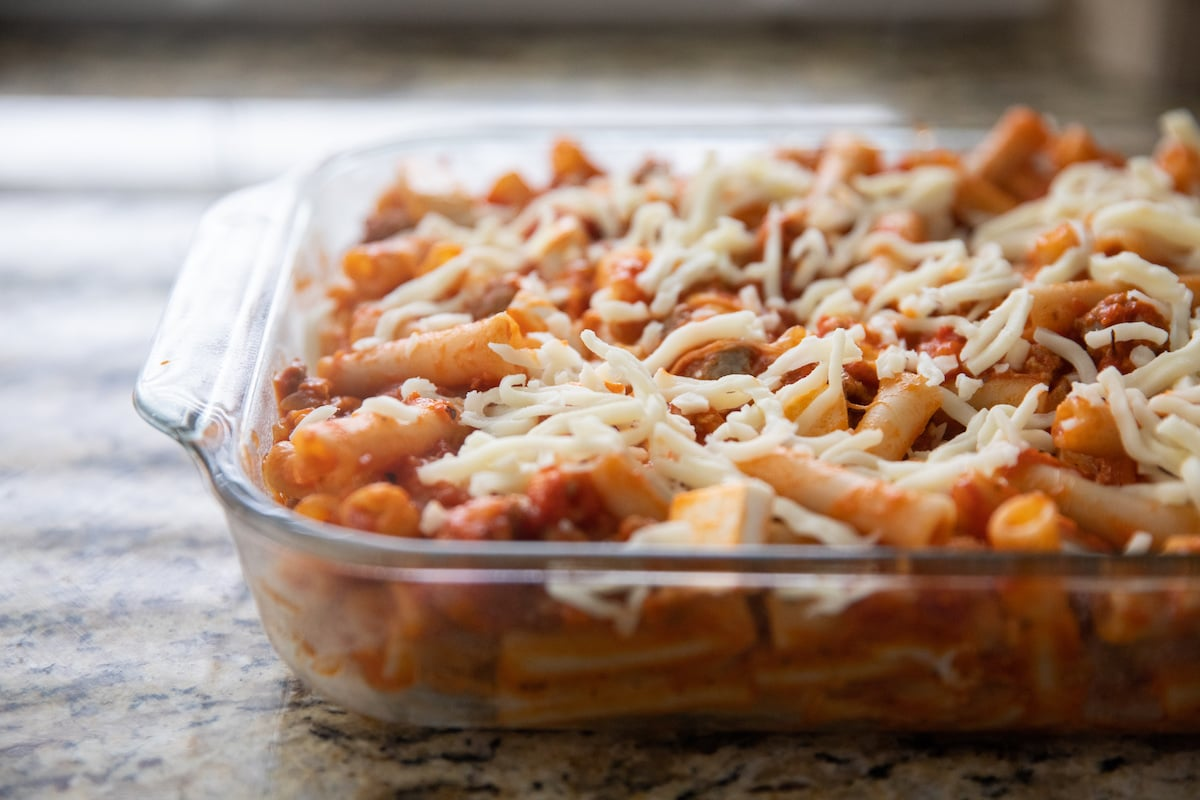 baked ziti topped with cheese in baking dish before baking