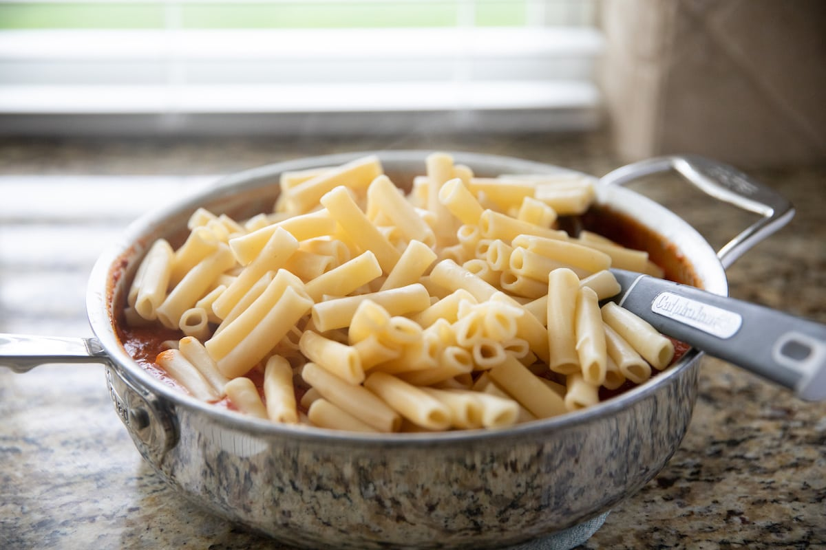 ziti pasta added to deep skillet with sauce