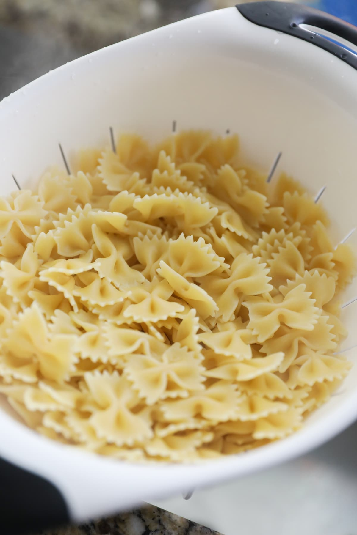 cooked bow tie pasta in colander