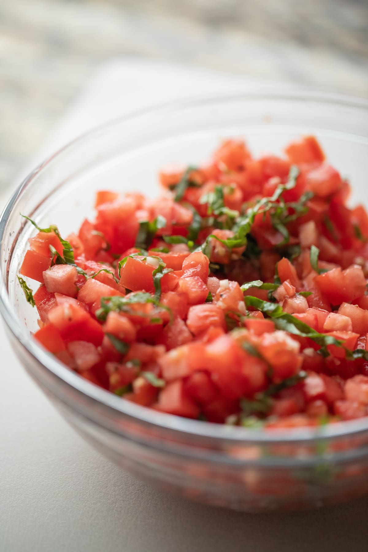 diced tomatoes, garlic and basil in glass bowl