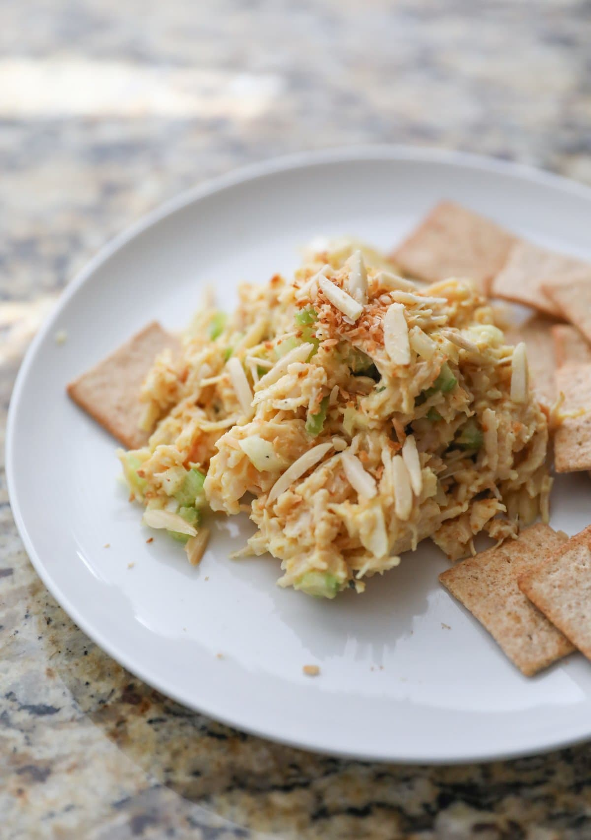 curry chicken salad with crackers on a white plate