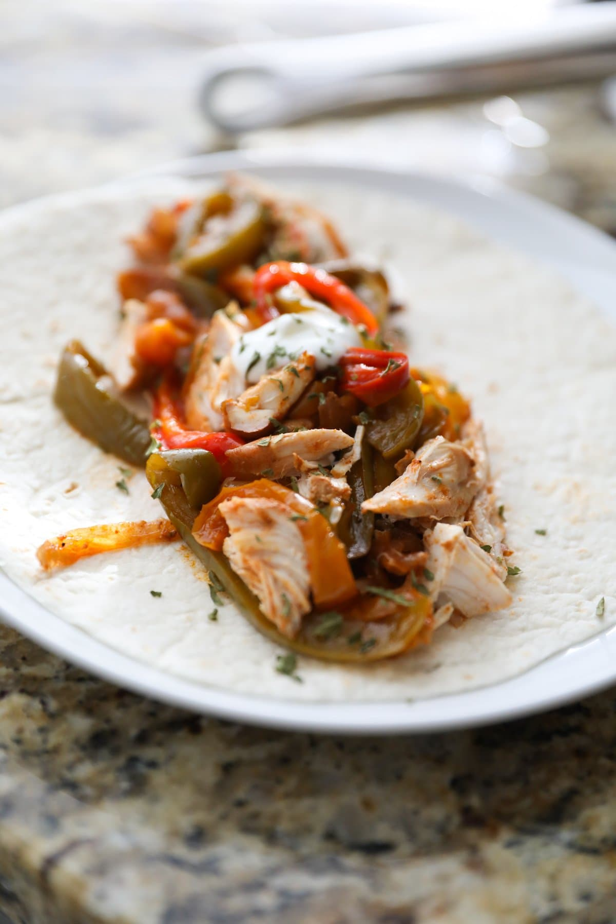 chicken fajita mixture on a tortilla on a white plate