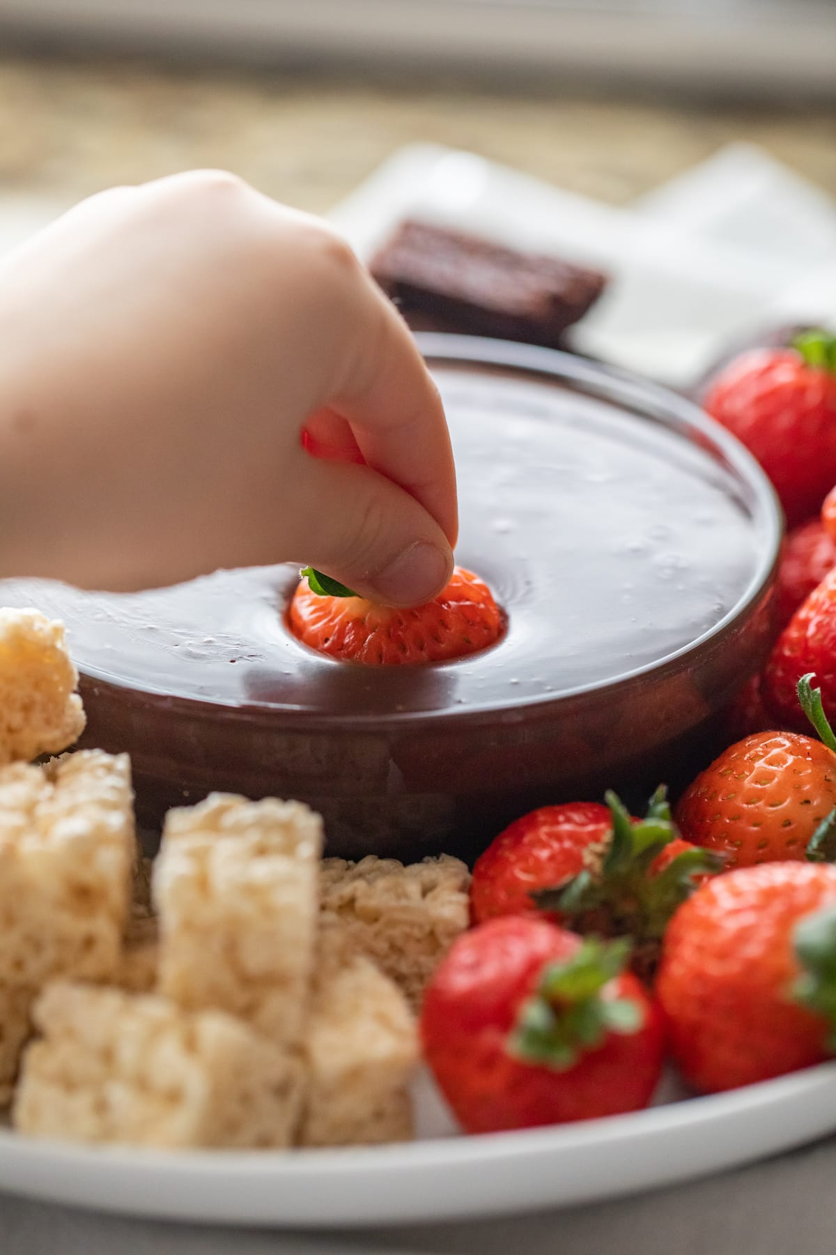 dipping fresh strawberry into bowl of dipping chocolate