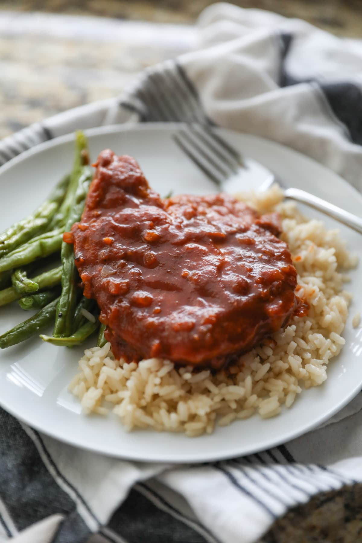 pork chop on white plate with rice and green beans