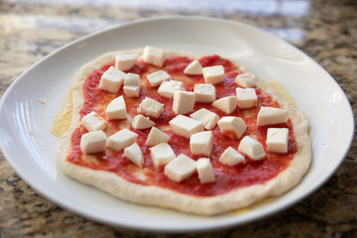 unbaked margherita pizza on plate
