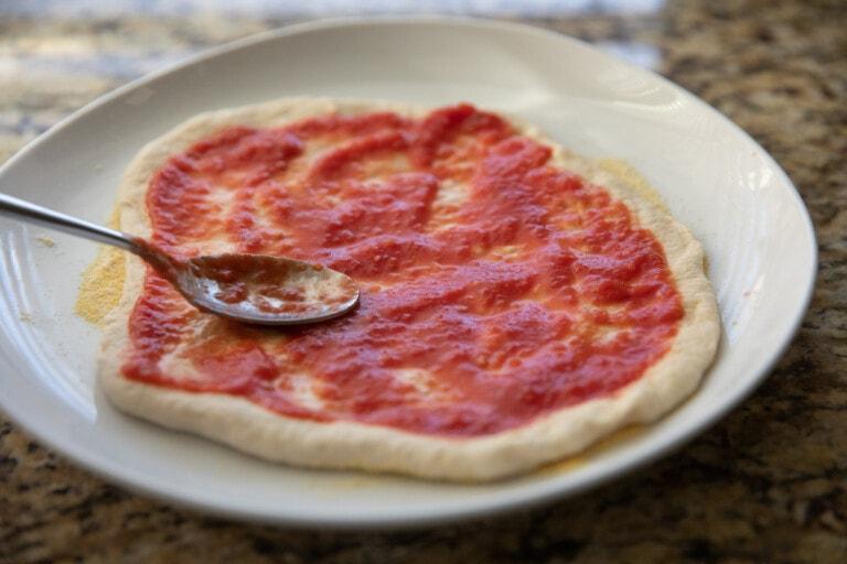 spreading margherita pizza sauce onto pizza dough