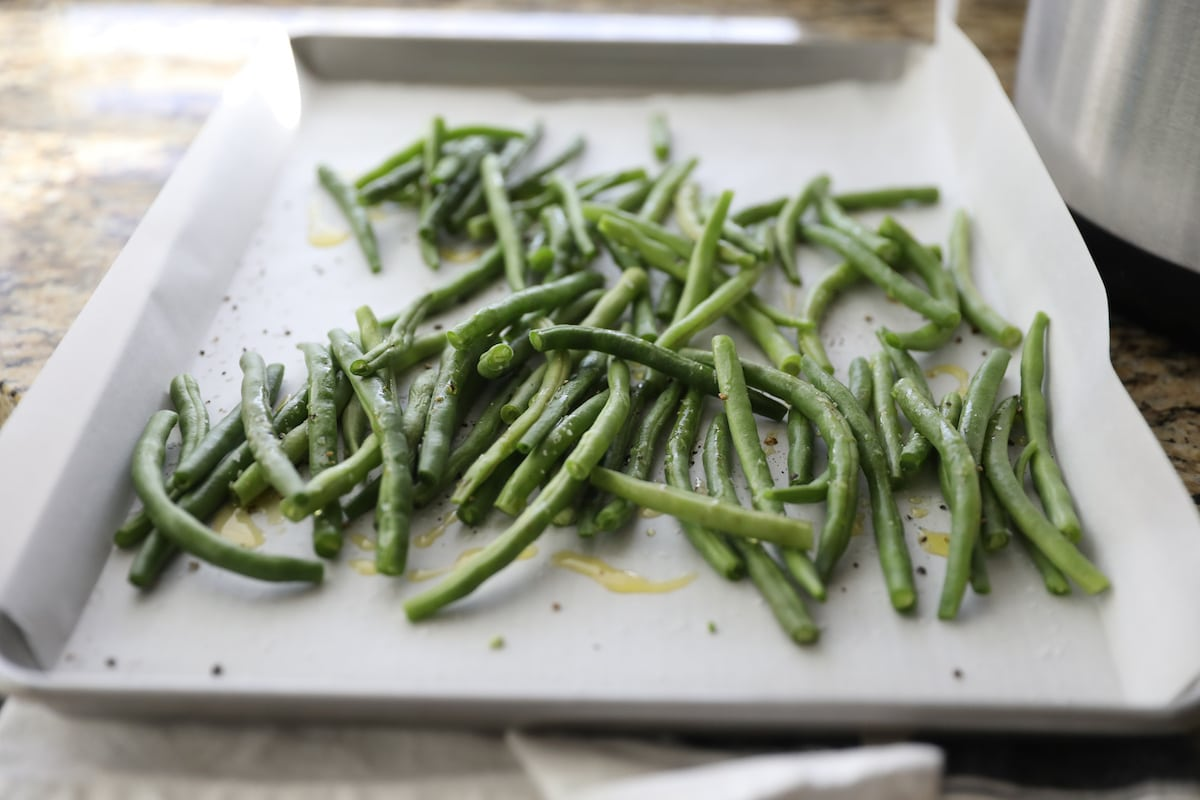green beans on baking sheet with olive oil, salt and pepper