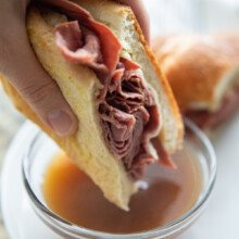 dipping french dip sandwich in au jus