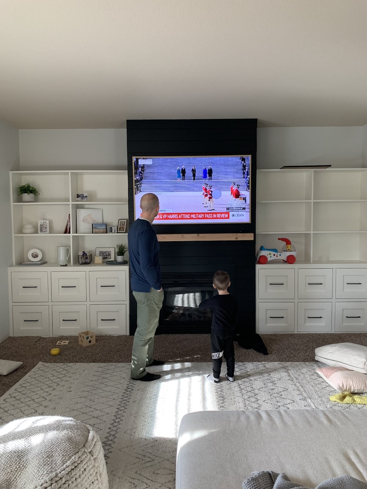 dad and son standing watching tv