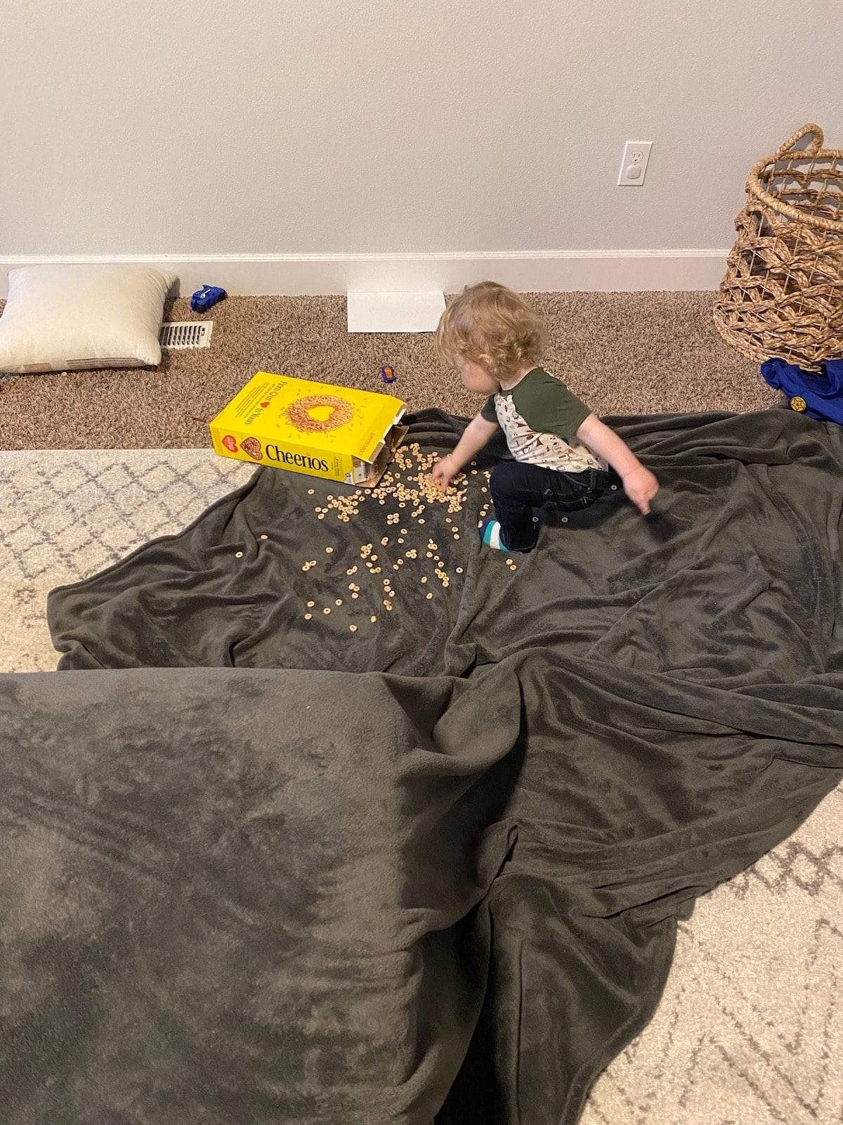 baby with dumped cheerios on blanket