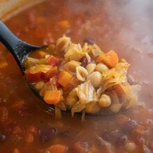 ladling minestrone soup out of pot