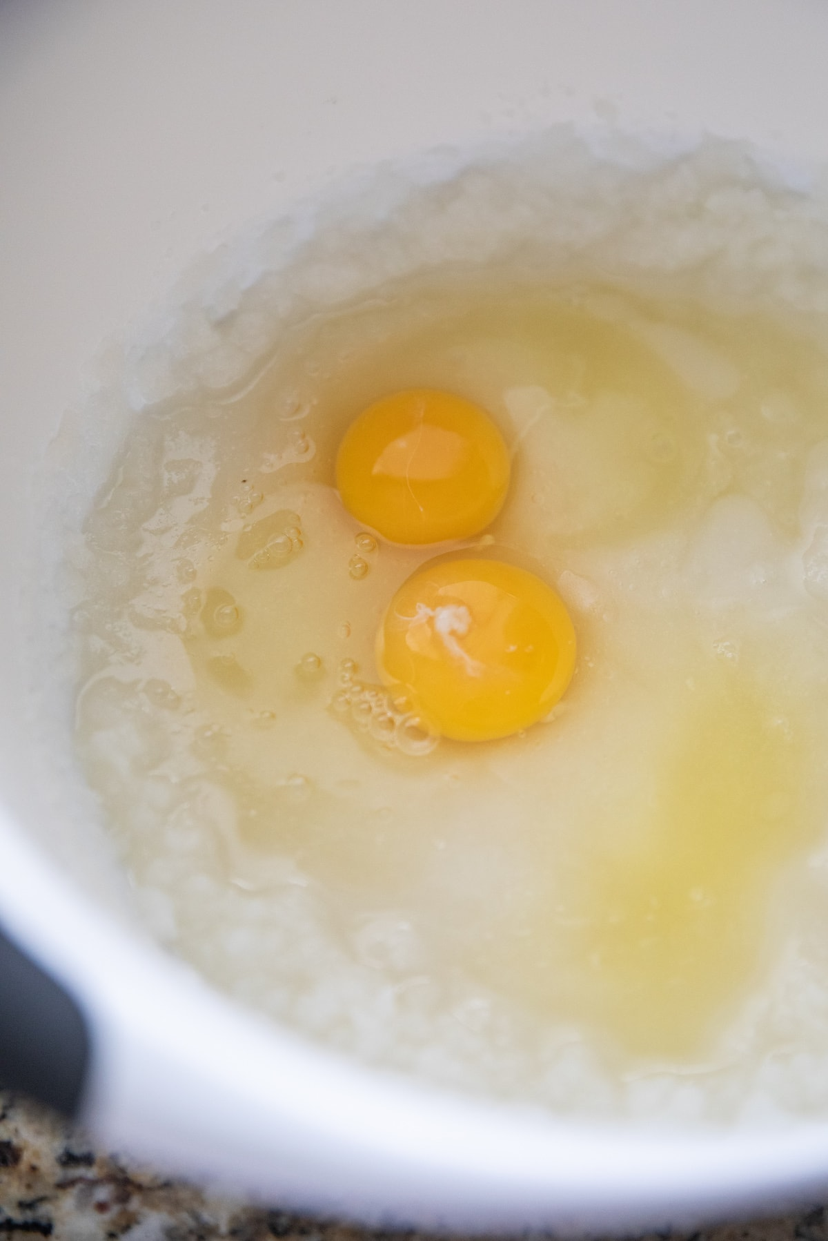 eggs in bowl with sugar and oil