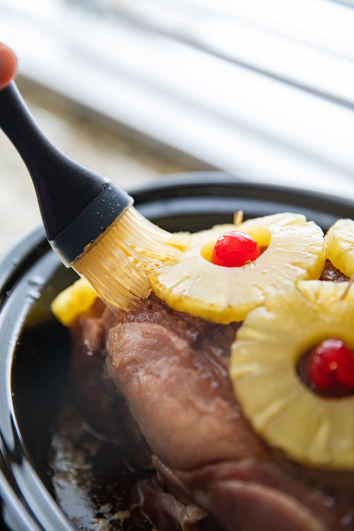 brushing ham in crockpot with glaze