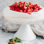strawberry pavlova on a white cake stand