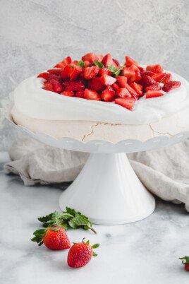 strawberry pavlova on a white cake stand